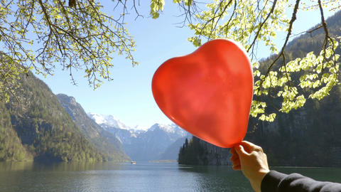 Mountains through red balloon in shape of heart Footage