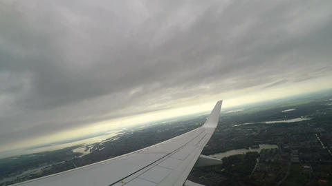 Airplane wing window view, after takeoff from airport, flying above city ビデオ