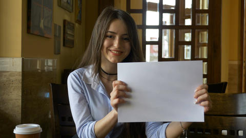 Young woman showing a white blank copy space page in a coffee shop Footage