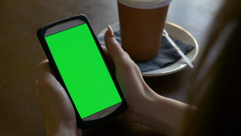 Closeup hands of woman holding smart phone with chroma key green screen in a caf Footage