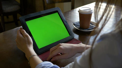 Woman sitting at a table using green screen tablet pc and making zoom in and out Footage