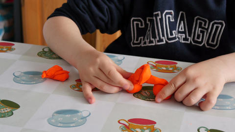 Child Modeling Orange Clay Filmmaterial