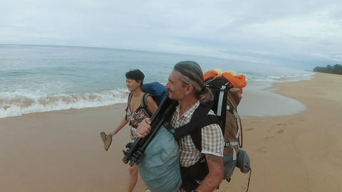 Tourists with backpacks go on the shore Footage