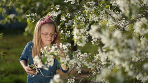 Adorable girl enjoying smell of spring garden Footage