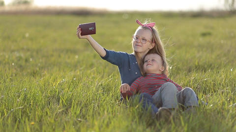 Smiling siblings taking selfie in the meadow Footage