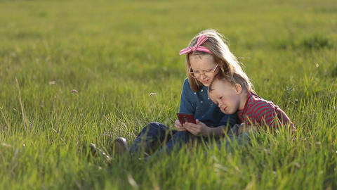 Cute kids playing on smartphones sitting on grass Footage