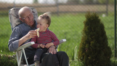 Grandfather giving banana to his grandson outdoor Footage
