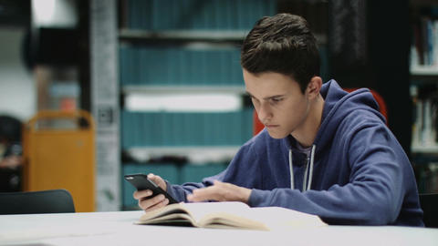 Boy studying in library, texting with smartphone Footage