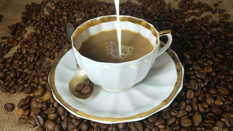 Pouring milk into the cup of fresh brewed coffee in slow motion Footage