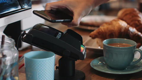 Payment with smart phone in café Live Action