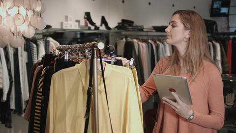 Small business owner in clothes shop ordering inventory on digital tablet Footage