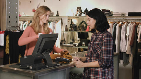 Consumer purchasing at till in clothes shop Live Action