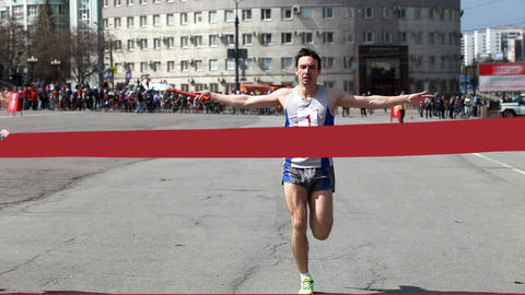 Athlete comes to the finish and tears the ribbon in the city competitions on the