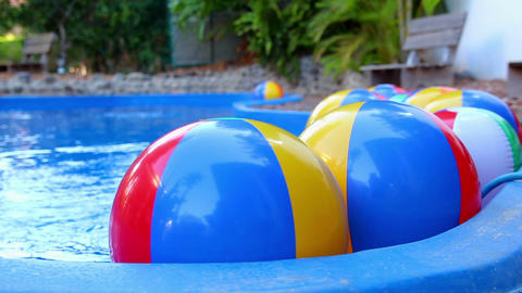 Colorful beach balls floating in pool Footage