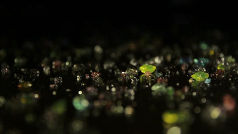 Colored crystals scattered on a table. A ray of light reveals them Footage