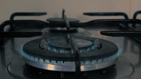 Frying pan being put on a kitchen gas stove with gas burning - Dark closeup