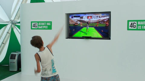 Backside View Teenager Plays in Virtual Sports Game Footage