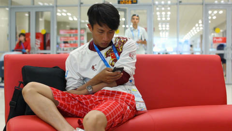Asian Teenager Sits on Red Sofa and Plays on Phone Footage