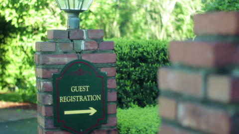 Boy walks past guest registration sign into bed and breakfast inn Footage