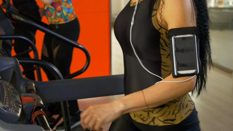 Closeup view of woman body adjusting smartphone headphones while exercising on g Footage