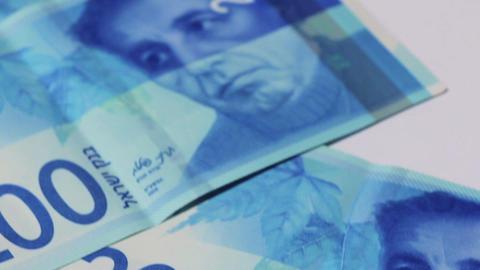 Stack of Israeli money bills of 200 shekel - Tilt down Footage