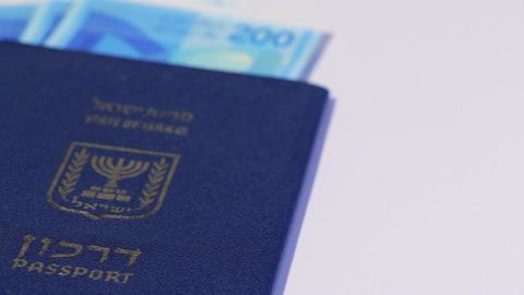 Stack of israeli money bills of 200 shekel and israeli passport - Pan left Footage