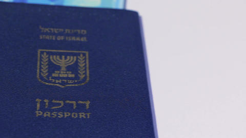 Stack of israeli money bills of 200 shekel and israeli passport - Pan left Footage
