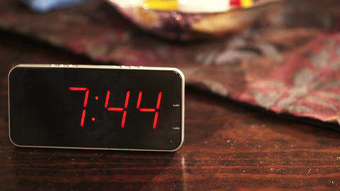 Close-up of a digital clock placed on wooden table when the time's passing Footage
