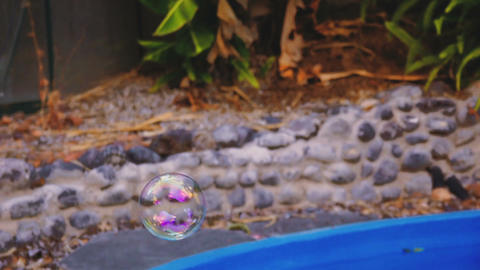 Soap bubbles fly over a swimming pool and jumping on the water Footage