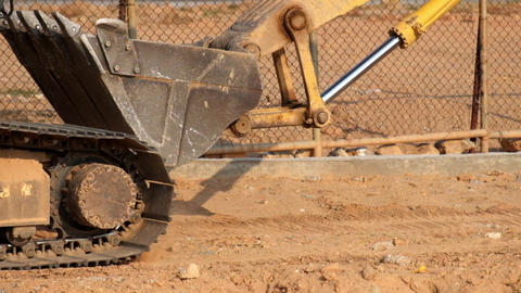 Excavator driving on a dusty road. Bucket close up. Video with original audio Footage