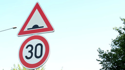 traffic signs - speed limit 30 and speed humps - urban street with passing cars  Footage