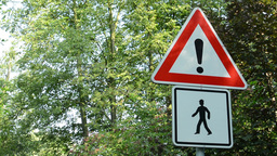 traffic signs - attention:pedestrian(walkers) - green trees in background Footage