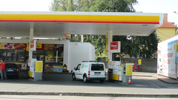 gas station Shell in the city - with cars and people. Passing cars with forest.  Footage