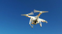 White remote controlled drone equipped with high resolution video camera hoverin Footage