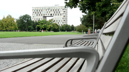 park (grass, trees) - benches in row - modern building and people in the backgro Footage