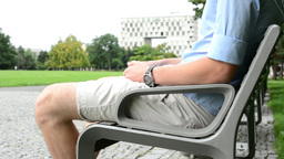 man sitting in the park on bench - pavement - park (trees and grass in the backg Footage