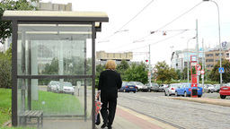 empty tram stop - old woman walking around - parking lot with buildings in backg Footage
