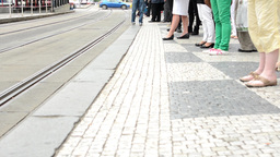 people wait at the tram stop - in the city - detail of legs - passing cars in th Footage