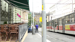 city: urban street - passing tram and empty outdoor seating in the restaurant Footage