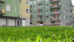 high rise block of flats with green grass a parked cars - slider move Footage