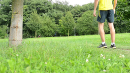 man sports - running - man warming up and then start running - green grass with  Footage