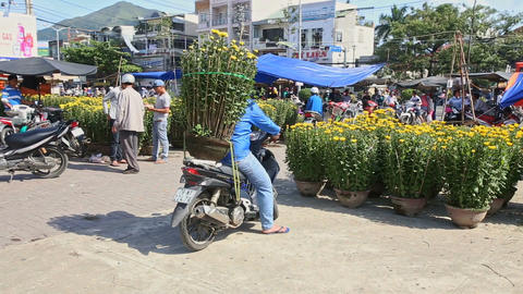 Camera Moves Around TET Flowers Market Man Sits on Scooter Footage
