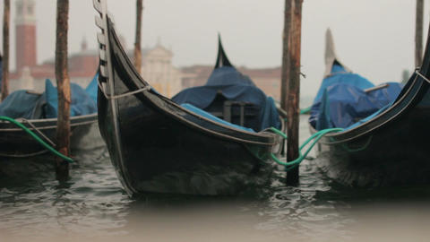 Close-up gondolas sway on the waves in Venice Live Action