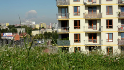 green grass with city (buildings: high-rise block of flats) in the background -  Footage
