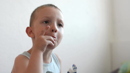 little boy(child) swings and eats candys - white wall in the background Footage