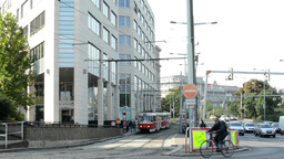 modern building with trams and passing cars on the urban street - nature (trees) Footage