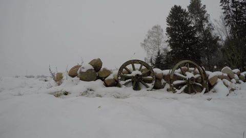 Two antique wooden wheels in the snow by the wall of stones, time lapse 4K Footage