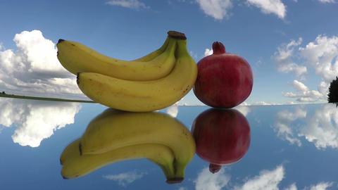 Three bananas and a pomegranate placed on mirror glass under cloudy sky, time la Footage