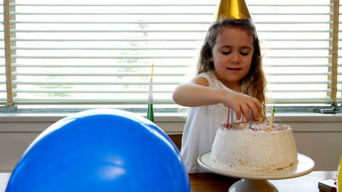 Girl placing candles over birthday cake Live Action