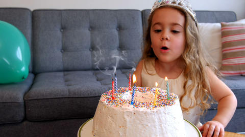 Girl blowing candles on birthday cake Live Action